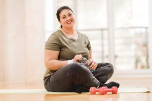 Mid adult fat woman resting after exercising. She is sitting on the floor and looking at the camera.